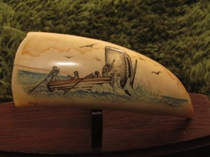Scrimshaw on whale tooth by Philip Hoyte depicting a skiff with whalers and a sperm whale breaching the water beside them.
