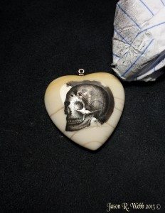 Skull scrimshaw on ivory heart with left half of the ink wiped away, the right half still covered by initial inking.