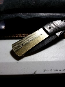 Damascus folder with the bone handle removed and Jason's careful cleaning about half way through