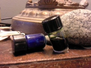 Tipped ink vial (left) and one with poster putty on the bottom holding it fast.