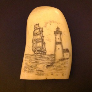 Rounded whale tooth with a ship and a lighthouse scrimshawed on the one side.