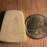 Lighthouse stippled onto galalith cabochon next to a quarter