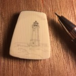 Scrimshaw lighthouse on galalith with tool to the right